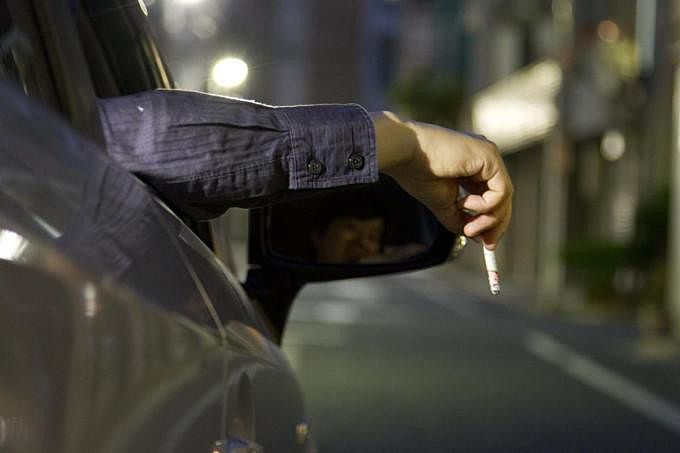 運転中に車の窓から手を伸ばしタバコの灰を捨てる人