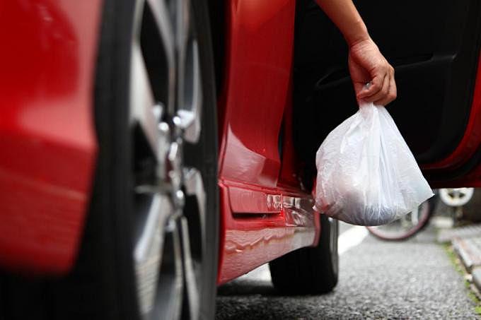赤い車の中からゴミをポイ捨てする人