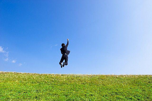 青空に向かってジャンプする成人の日を迎えた人