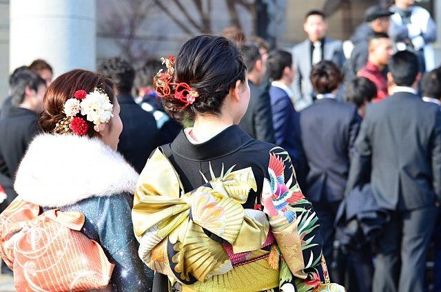 成人の日に成人式の会場に向う振り袖姿やスーツ姿の向かう成人たち