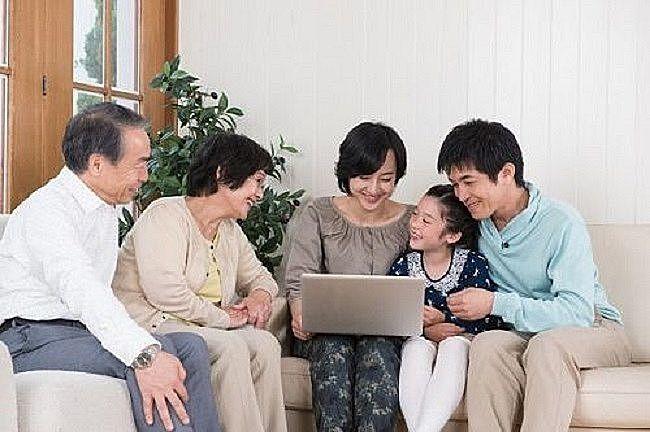 パソコンを見ながら不動産について話し合う家族