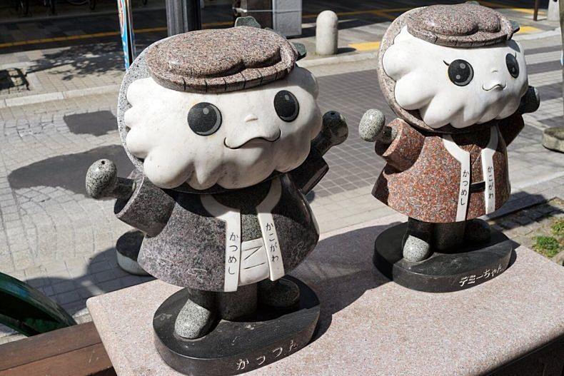 加古川駅前ベルデモール商店街に立つかつめしのイメージキャラクター、かっつんとデミーちゃん