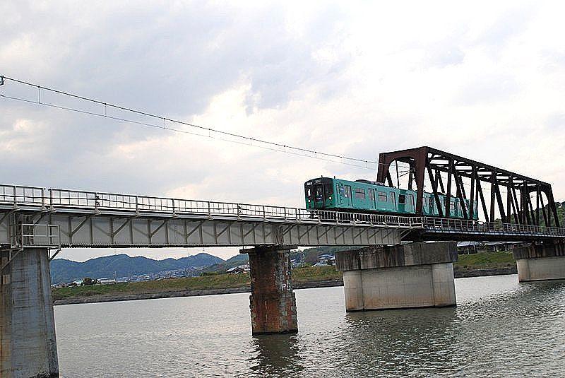 加古川に架かる国包の鉄橋を、エメラルドグリーンの電車がゆっくりと渡っています。