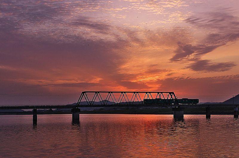 夕暮れの国包の鉄橋を渡る加古川線の電車。