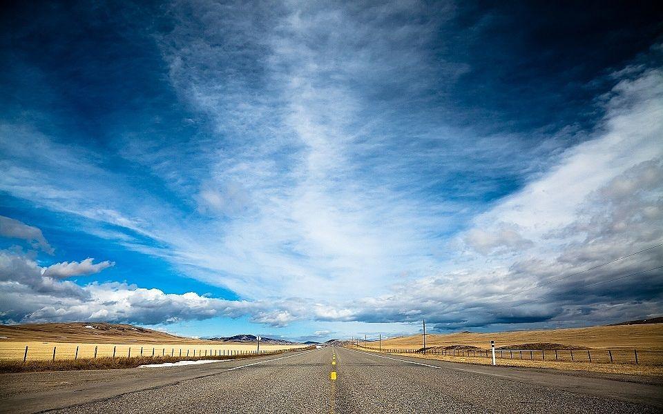 青空の下にはるか向こうまで続く一本道。