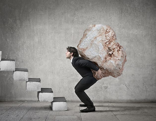 思い岩をかついで階段を登ろうとする人。