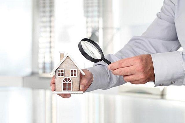 虫眼鏡で家の模型を観察している人。