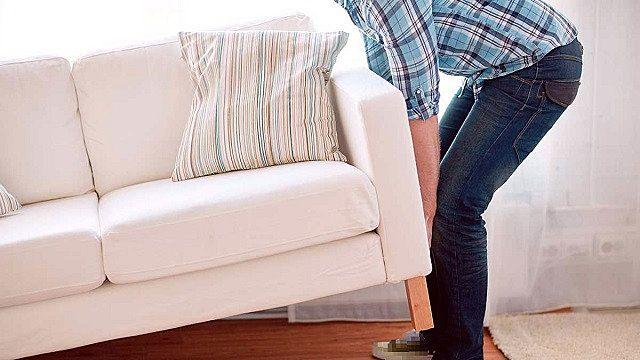 ソファーを移動させる男性。
