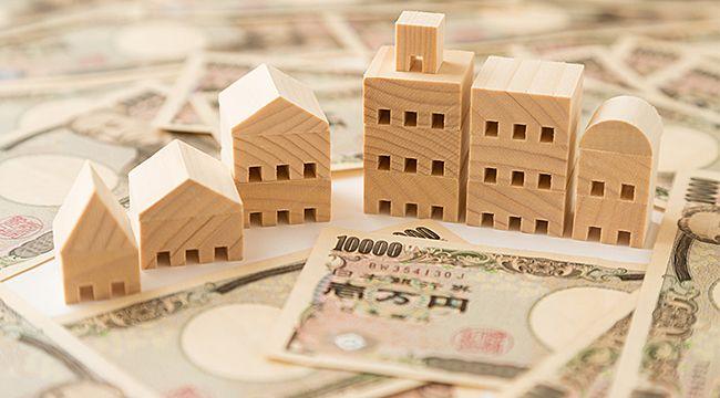 建物の模型と一万円札で不動産買取りをイメージ
