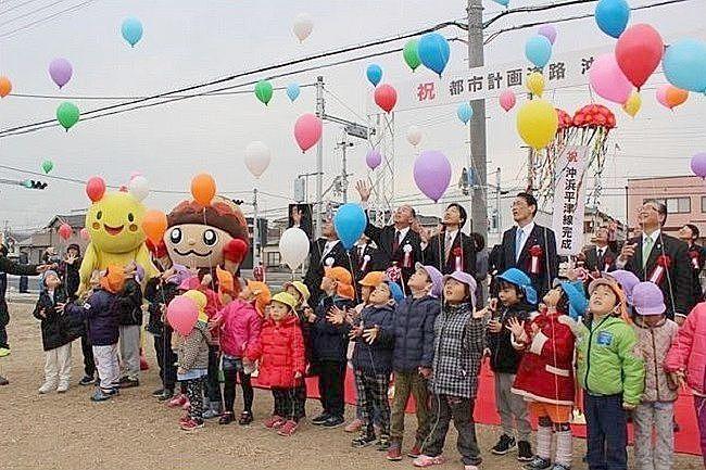 沖浜平津線の完成式典で風船を空高く飛ばしている園児たち